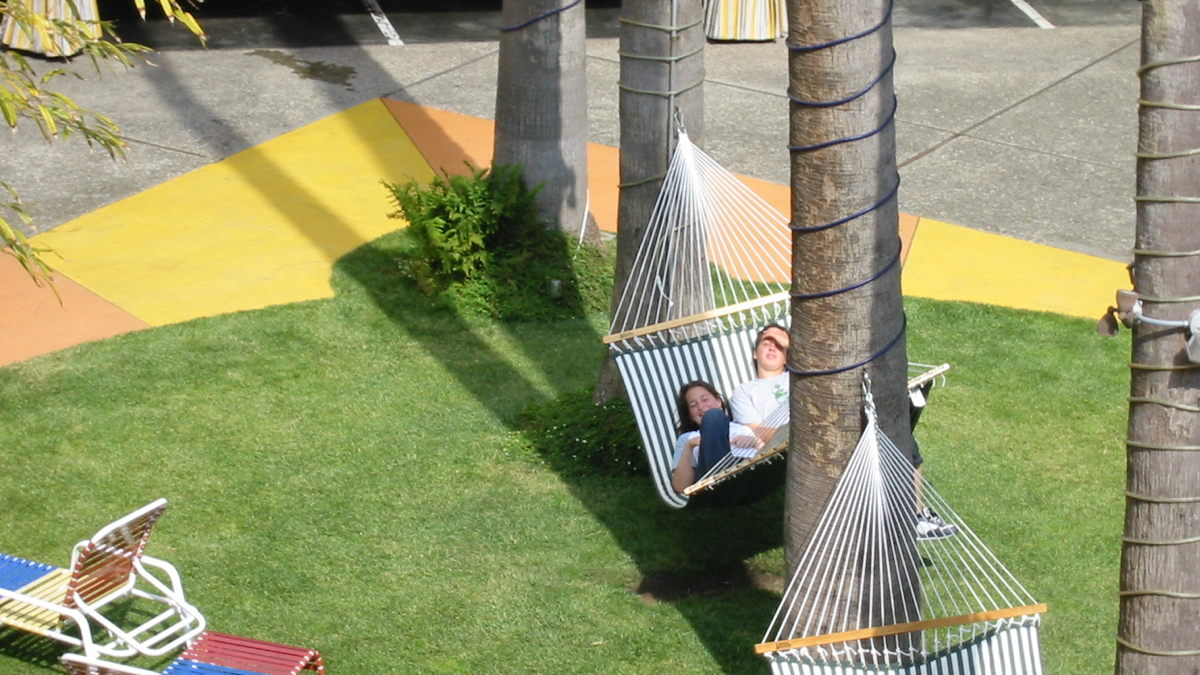 James and Rachel lying in a hammock in the courtyard of the Hotel Del Sol in San Francisco